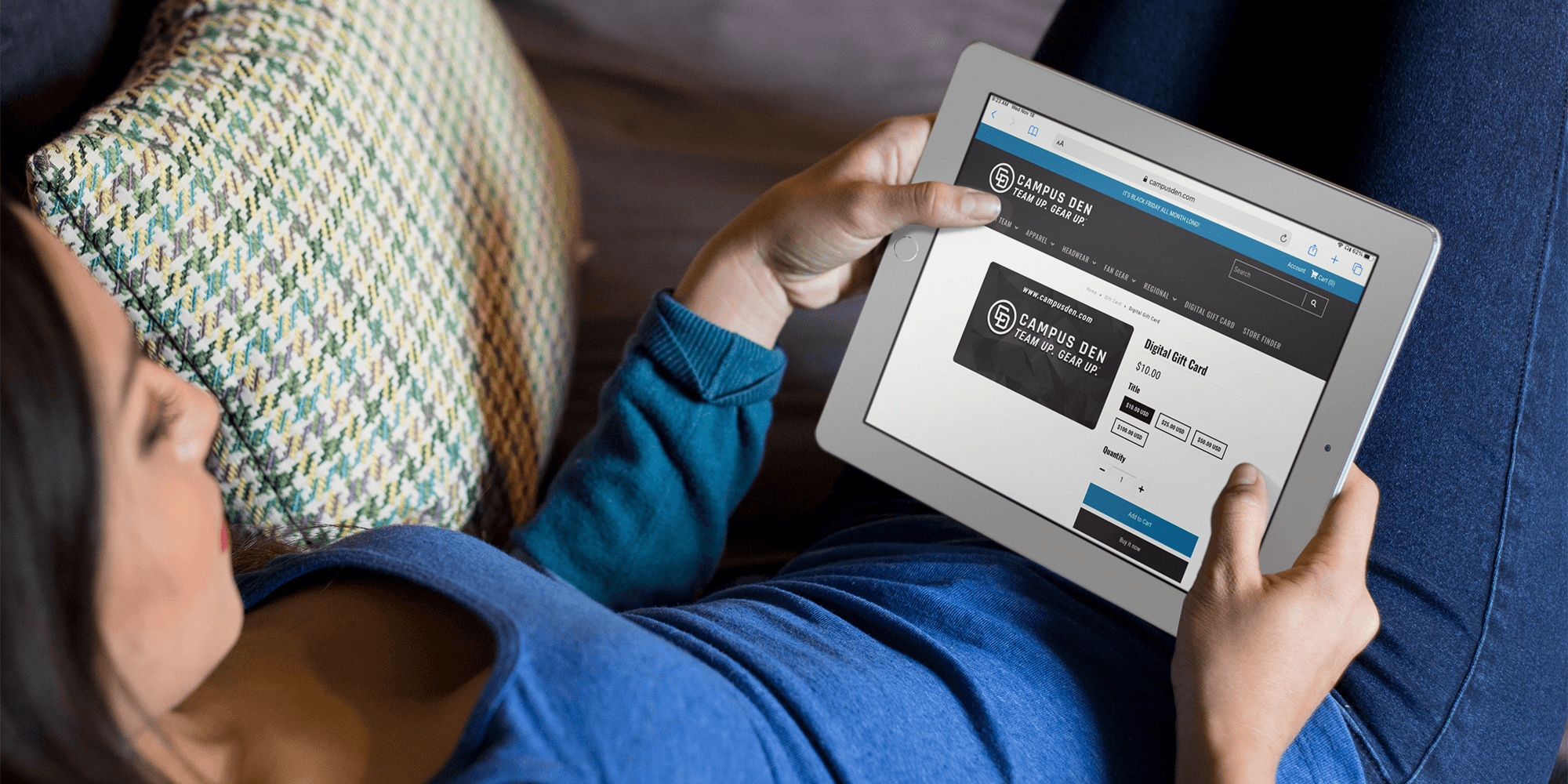 a woman chilling on a couch shopping for a Campus Den giftcard on an ipad.png