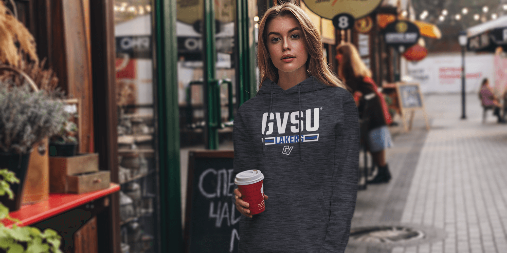 a woman wearing a Campus Den GVSU hoodie and holding a coffee